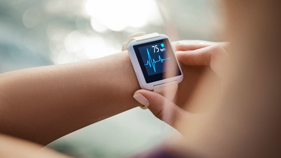 A woman checking her heart rate on a fitness tracker.