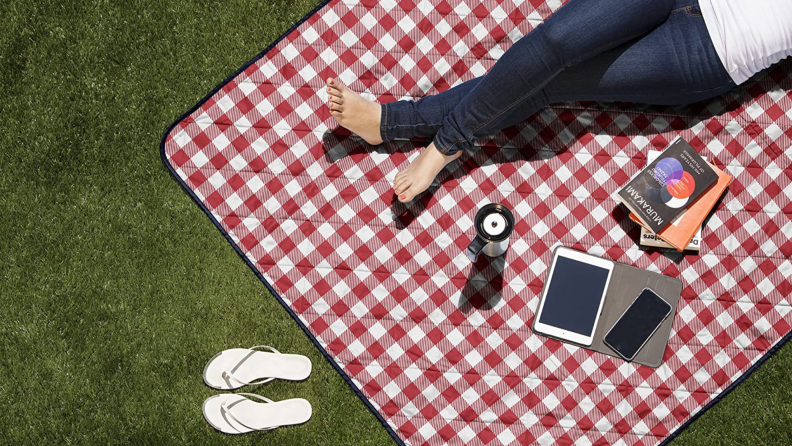 A person lays on a picnic blanket in the grass.