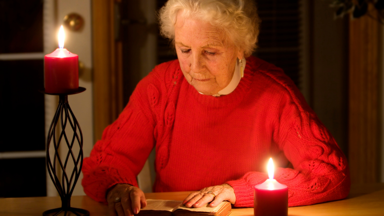 Older woman reading next to lit candles in a dark room