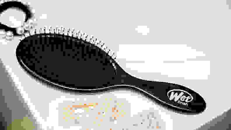 A black oval hair brush sitting on a sink with hair clips next to it.