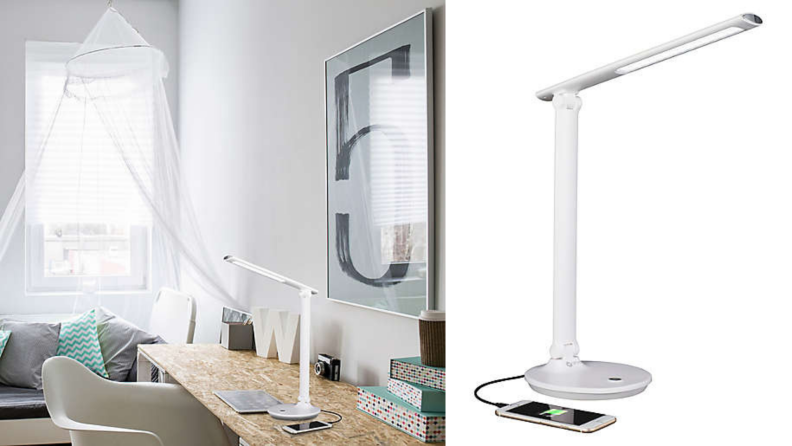 An Ottlite reading lamp sits on a desk in a white room.