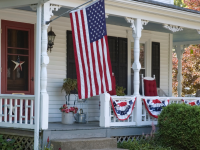 White house with patriotic decor on porch.