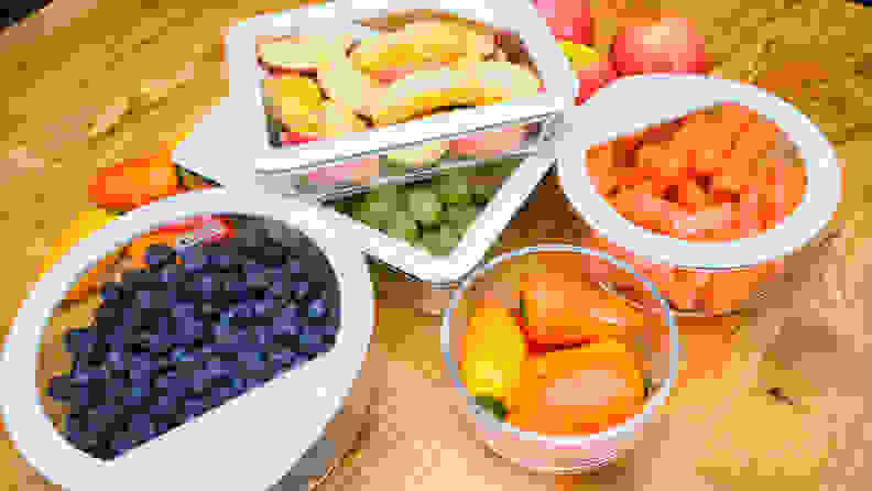 A collection of Pyrex containers filled with various fruits and vegetables.