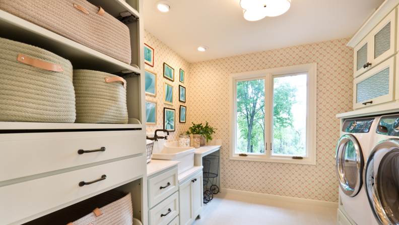 This photograph shows how wire, woven, or rattan baskets can help your laundry room look chic and serve a purpose. Decorative pictures are hung on the wall opposite a washer and dryer; the sun is shining outside the window.