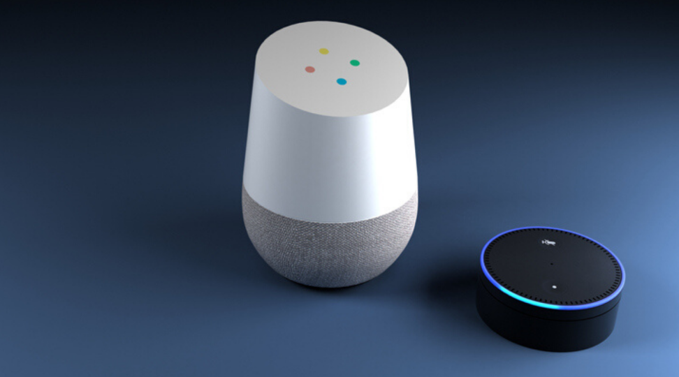 A Google Home speaker sits next to Amazon's Echo Dot speaker.