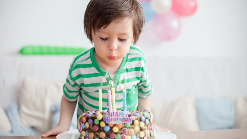 Boy blowing out birthday candles on cake