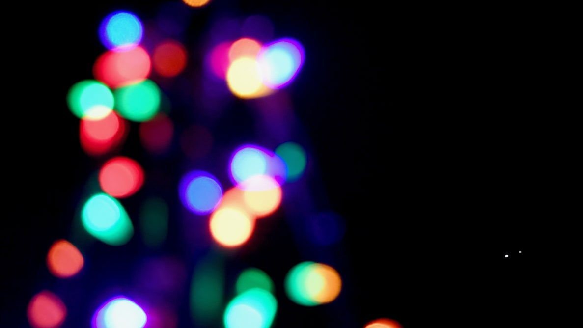 Colorful holiday lights are photographed out of focus.