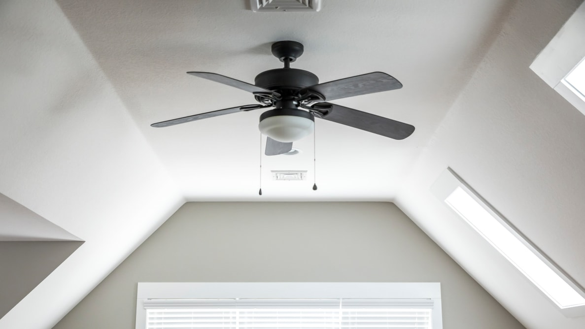 A ceiling fan hanging from a white, slanted ceiling