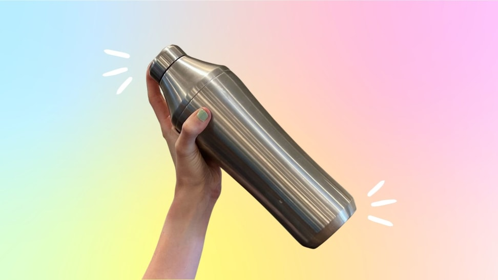A hand holds a stainless steel cocktail shaker against a rainbow gradient background.