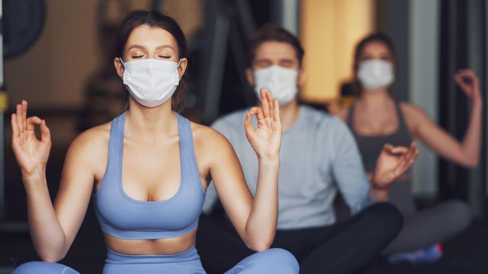 three people taking a yoga class wearing masks