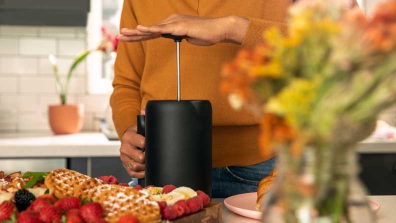 A person is plunging down a French press to make coffee in a kitchen. A plate of Belgian waffles and strawberries are on display as well.