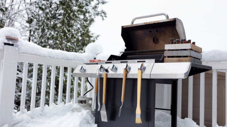 Open grill with grill accessories attached on snowy outdoor deck