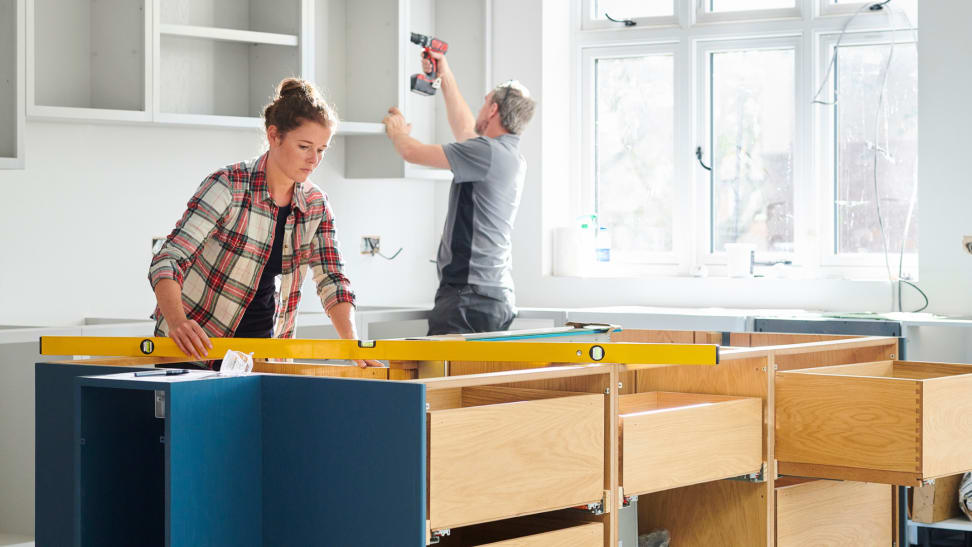 Man and woman working together to remodel kitchen.