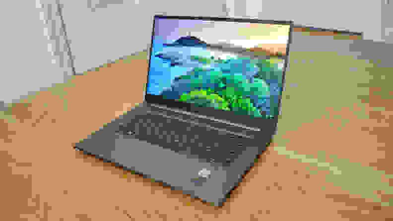 An open laptop sitting on a hardwood floor
