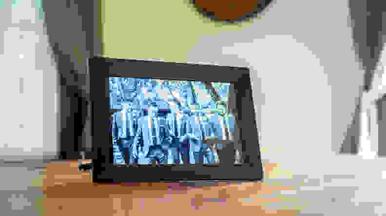 The Nixplay digital picture frame displays a black-and-white image of groomsmen.