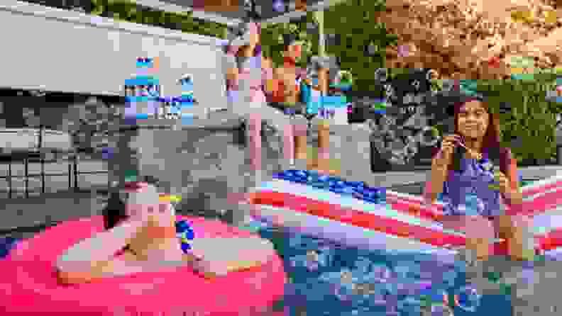 Kids in a pool blowing bubbles