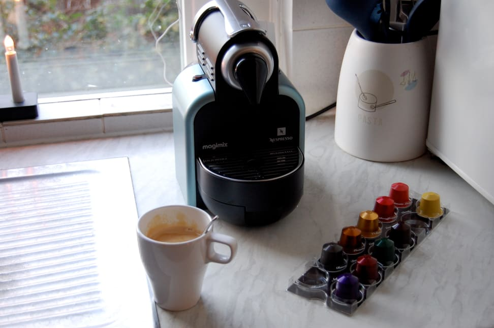 A Nespresso coffee maker with pods and cup of coffee