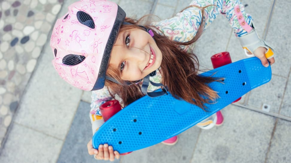 Girl with a skateboard wearing a helmet