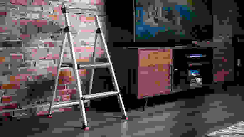 A step stool stands by a TV in front of a brick wall