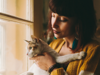A woman holds a cat as it looks out the window