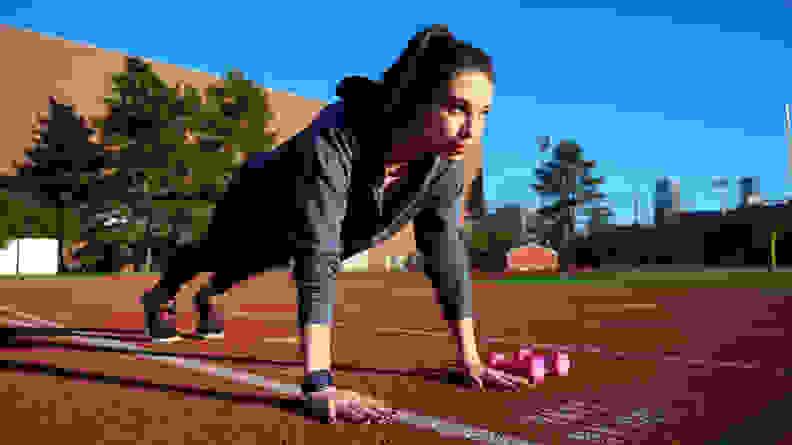 woman wearing fitbit doing plank