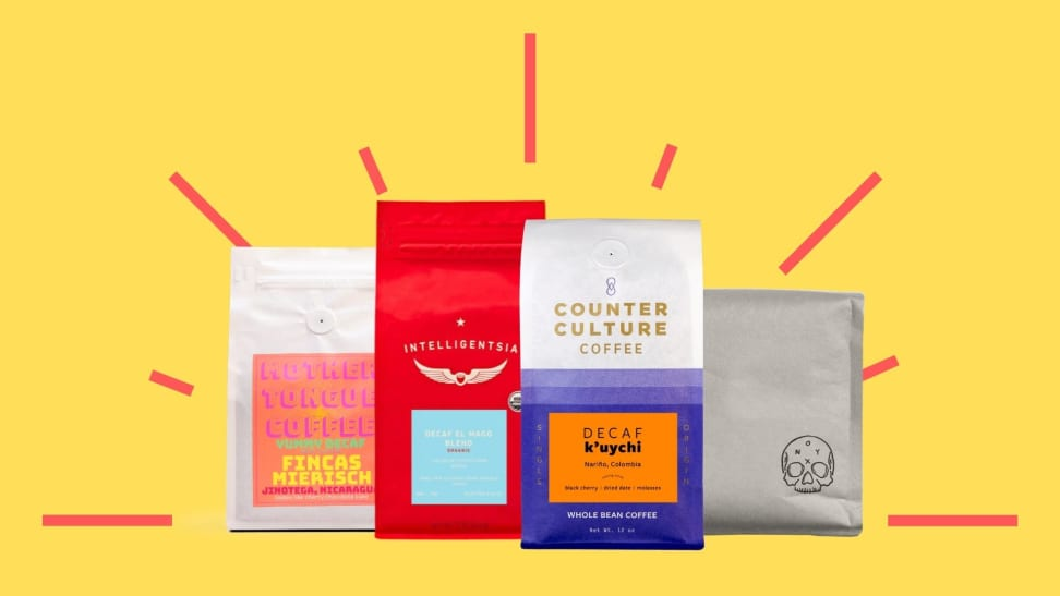 Four colorful bags of decaf coffee against a bright yellow background.