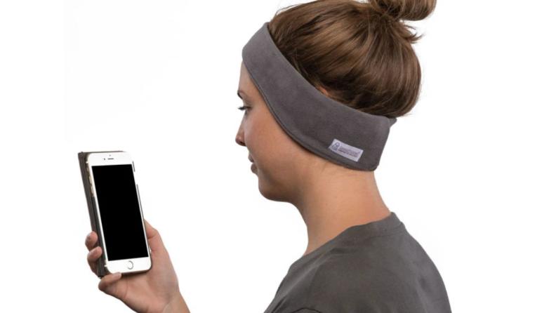 Woman wearing gray bluetooth sleep headphones while holding smartphone.