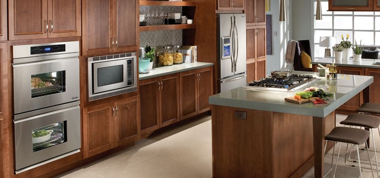 Earth-toned kitchen designed around Dacor's Distinctive Series, including a 30-inch double oven, 24-inch microwave, and a 36-inch gas cooktop.