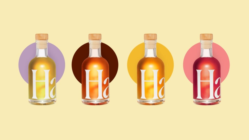 Four colorful mini bottles of assorted aperitifs are arranged in a straight line across a pale yellow background.
