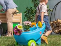 A child pulls a toy wheelbarrow full of plants