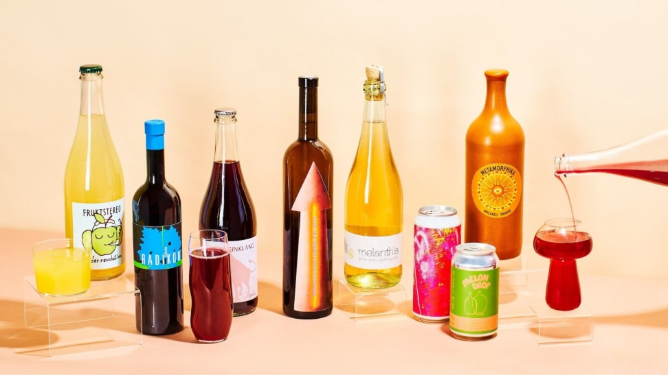 Assorted bottles and cans of various natural wine varietals, featuring brightly-colored labels.