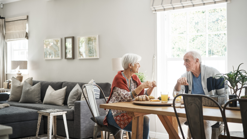 Senior couple sitting together having a discussion at dining room table in bright room surrounded by windows.