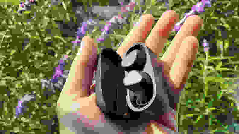 Jabra's all-black, matte earbuds sit in their open case in an open hand above green and purple flowers blown in a light breeze.