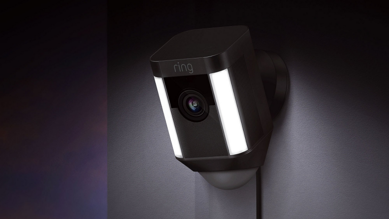 An image of a Ring security camera positioned on the side of a wall, shining down with the camera on.