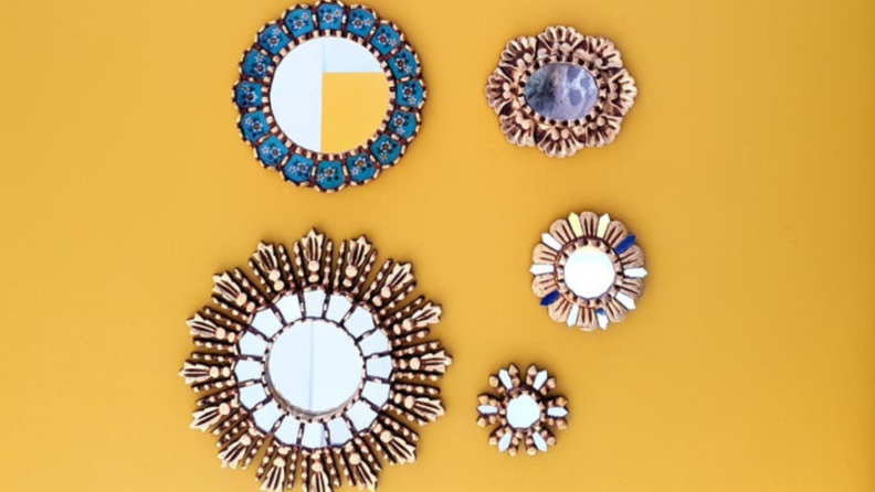 Set of five blue and gold gallery wall mirrors on a yellow wall