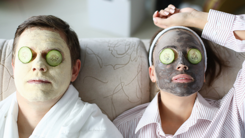 A couple luxuriates on the couch, each wearing a face mask with cucumbers over their eyes.