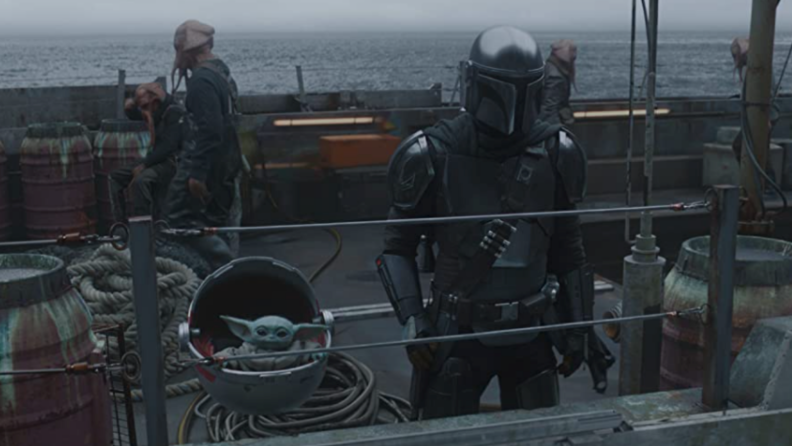 A still from the Mandalorian featuring Mando and Baby Yoda on a ship.