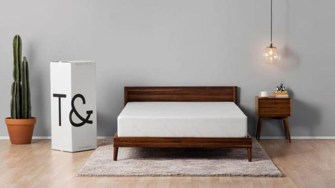 A bare Tuft and Needle mattress, sitting on a wooden bed frame in a master bedroom.