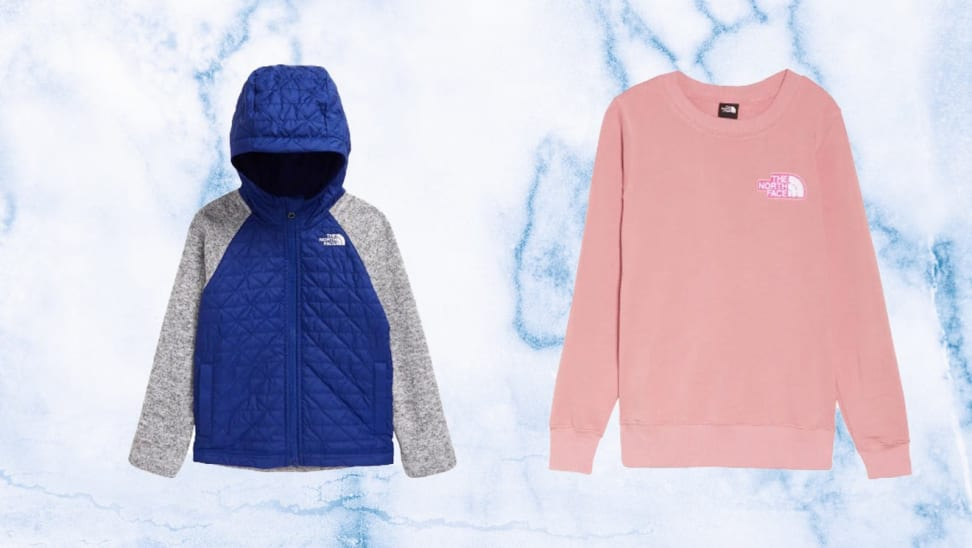 On right, gray and blue The North Face jacket in front of light purple background. On right, pink pullover sweatshirt from The North Face in front of light purple background.