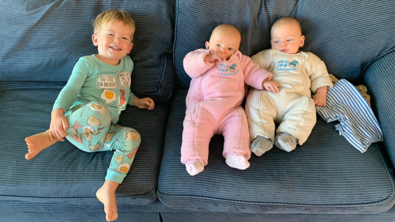 A toddler and two infants sit on a blue couch.