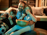 Dad and two kids watching a movie at home
