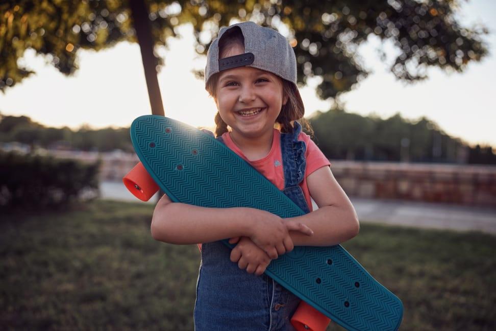A girl smiles as she hugs her Penny Board beginner skateboard for kids.