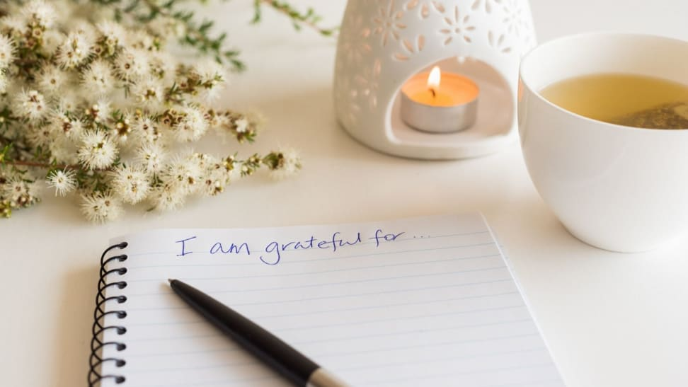 a gratitude journal open on table next to tea and a candle
