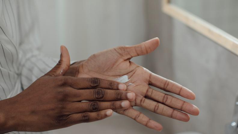 Person rubbing moisturizer into hands.