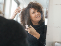 A woman spraying hairspray while looking in a mirror