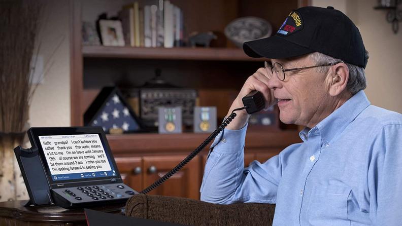 A senior talks on a phone with captions.