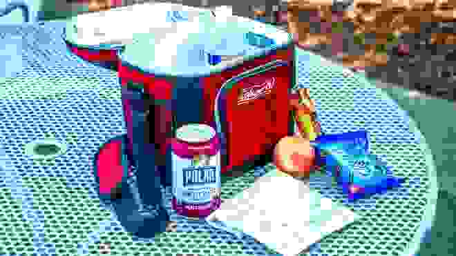 An open soft cooler with a water bottle in it on an outdoor picnic table, sitting next to a seltzer, snack bag, apple, granola bar, and cookies