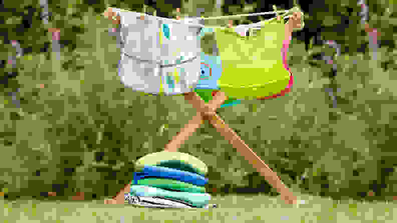 A variety of baby and toddler bibs drying on a rack outside