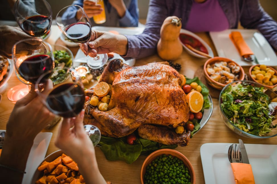 A group of people toasting with glasses of red wine over  a roast turkey.