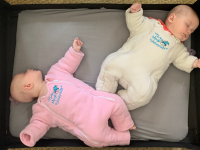 Two babies wearing Baby Merlin's Magic Sleepsuit lay down for a nap.